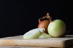 Whole and Sliced Onions on Chopping Board with Black Background Royalty Free Stock Image