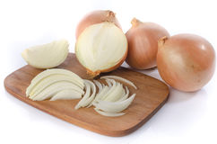 Whole and sliced onions on a cutting board Royalty Free Stock Photos