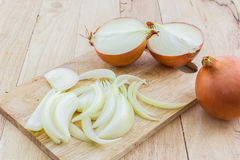 Whole and sliced onions. Whole and sliced onions on wooden cutting board Stock Images