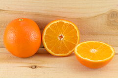 Whole and sliced orange on wooden table Royalty Free Stock Images