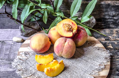 Whole and sliced peaches lying on cutting board Royalty Free Stock Photo