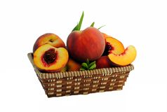 Whole and sliced peaches in a straw basket. With leaves Stock Photos