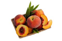 Whole and sliced peaches in a straw basket. With leaves Royalty Free Stock Photos