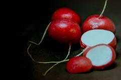 Whole and sliced radish on a black background. Create a beautiful contrast Royalty Free Stock Photos