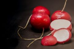 Whole and sliced radish on a black background. Create a beautiful contrast Royalty Free Stock Images