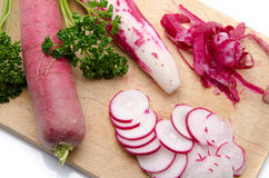Whole and sliced red radish on a wooden cutting board. Composition with whole and sliced red radish on a wooden cutting board Royalty Free Stock Image