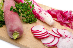 Whole and sliced red radish on a wooden cutting board. Composition with whole and sliced red radish on a wooden cutting board Royalty Free Stock Photography