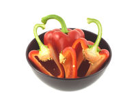 Whole and sliced ripe red peppers in green bowl isolated Royalty Free Stock Images