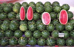 Whole and sliced watermelons at market stock image