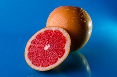 Whole and slicend on half grapefruit on a blue background, horizontal shot. Picture presents whole and slicend on half grapefruit on a blue background Stock Photos