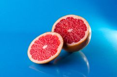 Whole and slicend on half grapefruit on a blue background, horizontal shot. Picture presents whole and slicend on half grapefruit on a blue background Stock Image