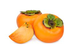 Whole and slices of fresh ripe persimmons isolated on white Stock Photo