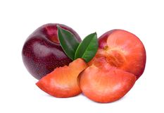 Whole and slices red plum with green leaves isolated on white royalty free stock photo