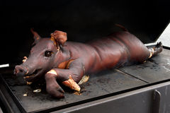 Whole smoked suckling piglet on hot griddle. Stock Image