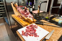 Spanish pork ham on wooden board with knife stock photo