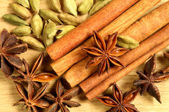 Whole spices. On wooden background - cinnamon sticks, anise stars and cardamon Stock Images