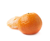 Whole tangerine next to peeled slices Stock Image