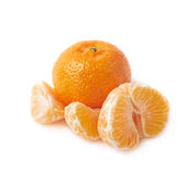 Whole tangerine next to peeled slices Royalty Free Stock Image