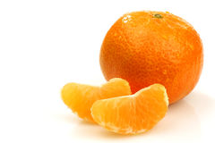 A whole tangerine and two slices. On a white background Stock Image