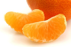 A whole tangerine and two slices Royalty Free Stock Images