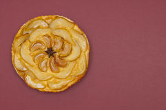 Whole tarte Tatin apple pear tart isolated on claret background Stock Photography