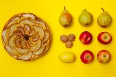 Whole tarte Tatin apple tart with fruits on yellow background Stock Images