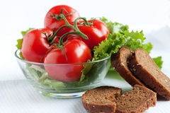 Whole tomatoes in a salad bowl and bread slices. Good health food Stock Photos