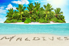 Whole tropical island within atoll in tropical Ocean and inscription 'Maldives' in the sand on a tropical island, Maldives. Whole tropical island within atoll royalty free stock photo