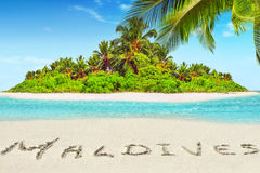Whole tropical island within atoll in tropical Ocean and inscription 'Maldives' in the sand on a tropical island, Maldives. Whole tropical island within atoll royalty free stock photography