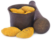 Whole turmeric with mortar and pestle Stock Images