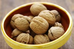 Whole walnuts. In bowl on wooden background Royalty Free Stock Photography