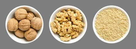 Whole, walnuts, kernel halves and ground walnuts in white bowls on gray background. Seeds of the common walnut tree Juglans regia, used as snack or for baking Stock Images
