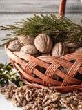 Whole walnuts and peeled walnut kernels near the wicker basket royalty free stock photography