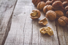 Whole walnuts on rustic background. Whole walnuts with shell on rustic wood background, toned Stock Photography