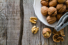 Whole walnuts on rustic background. Whole walnuts with shell on rustic wood background, top view Royalty Free Stock Image