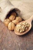 Whole walnuts in sackcloth bag and walnut kernels on wooden spoon. Walnut, kernel, sweet, arabian, closeup, , vegetarian, meal, organic, rustic, proteins Stock Photos