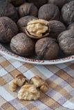 Whole walnuts and walnut kernels on table with tablecloth Stock Images