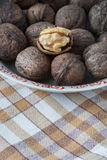 Whole walnuts and walnut kernels on tablecloth Stock Photos