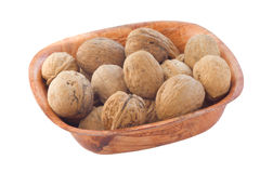 Whole walnuts in wooden plate. Royalty Free Stock Images