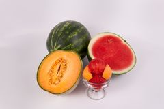Whole watermelon cantaloup and watermelon halves cup of melon fruit scoops. One whole green sweet watermelon one watermelon organic cantaloup halves glass cup of royalty free stock photography