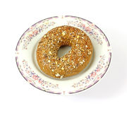 Whole wheat bagel on an old plate Stock Images