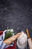 Whole wheat baguette in red basket with rosemary, flour and rolling pin over black grunge background. Top view, copy space, vertic Royalty Free Stock Photos