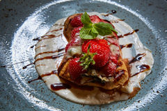 Whole wheat Belgium waffle topped with syrup, whipped cream, walnuts and freshly chopped strawberries Royalty Free Stock Photo