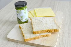 Whole wheat bread, cheddar cheese and matcha spread. Whole wheat bread and cheddar cheese on a wooden board with matcha spread Stock Photo