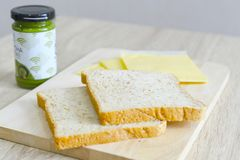 Whole wheat bread, cheddar cheese and matcha spread. Whole wheat bread and cheddar cheese on a wooden board with matcha spread in the background Royalty Free Stock Images