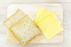 Whole wheat bread and cheddar cheese. On a wooden board Stock Images