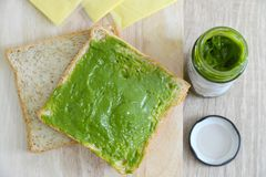 Whole wheat bread, cheddar cheese and matcha spread. Whole wheat bread and cheddar cheese on a wooden board with matcha spread on the bread Stock Images
