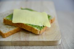Whole wheat bread, cheddar cheese and matcha spread. Whole wheat bread and cheddar cheese on a wooden board with matcha spread Royalty Free Stock Photo