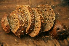 Whole wheat bread cut in slices on a wooden board at home Royalty Free Stock Photography