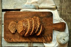 Whole wheat bread cut in slices on a wooden board at home Stock Photo